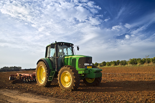tractor in a field with cloudy sky